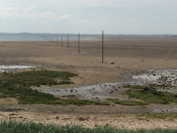 In the distance, towards the mainland, the tide is already moving in towards the Pilgrim's Way marker posts.